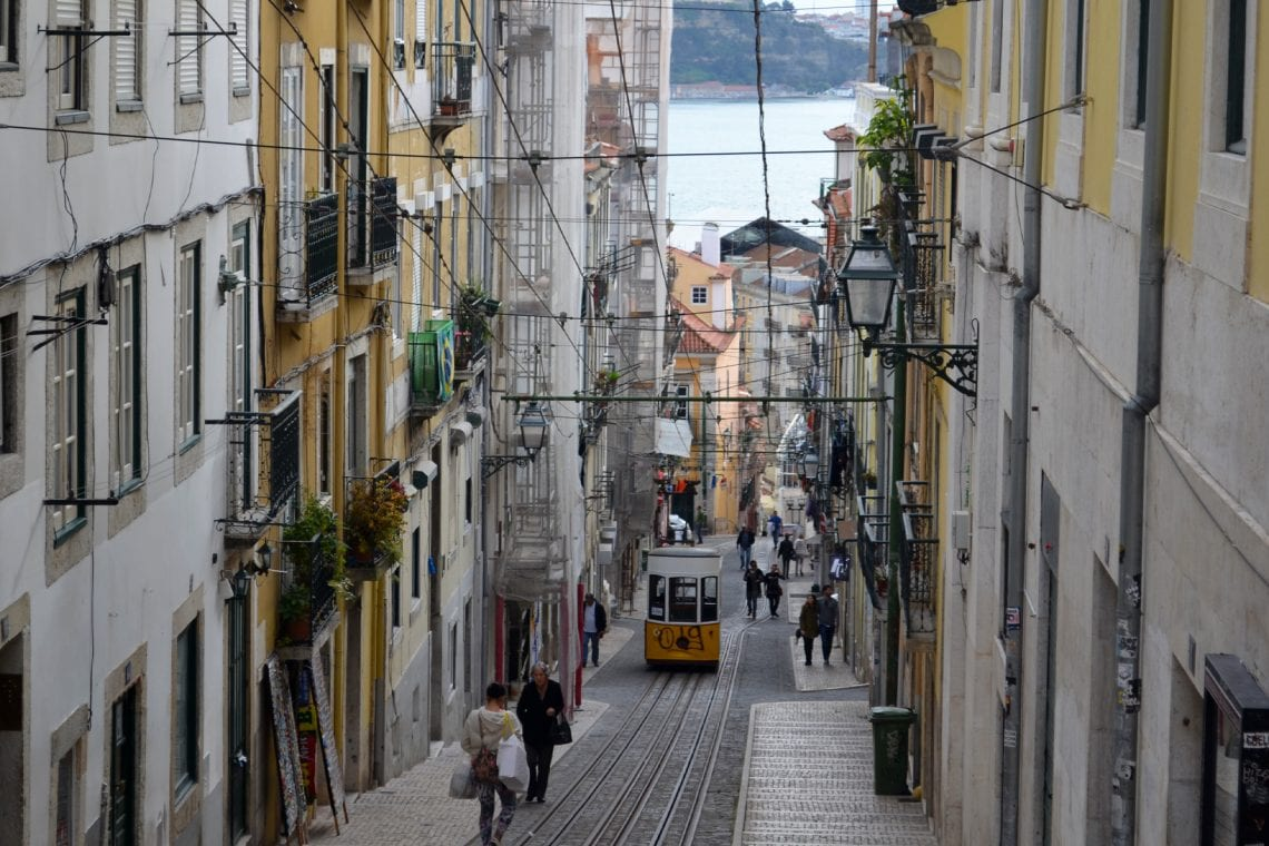 lisbon and porto tram going up steep road in lisbon